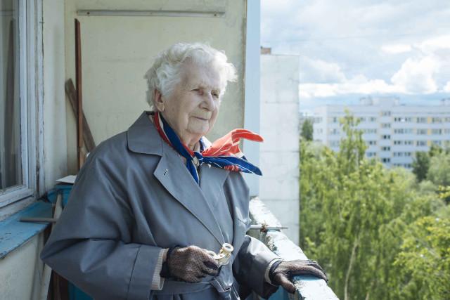 Антонова Александра Николаевна стоит на балконе, чтобы посмотреть на окрестности в бинокль.
